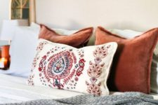 17 a knit blanket and colorful velvet pillows plus candles for a fall-inspired bedroom