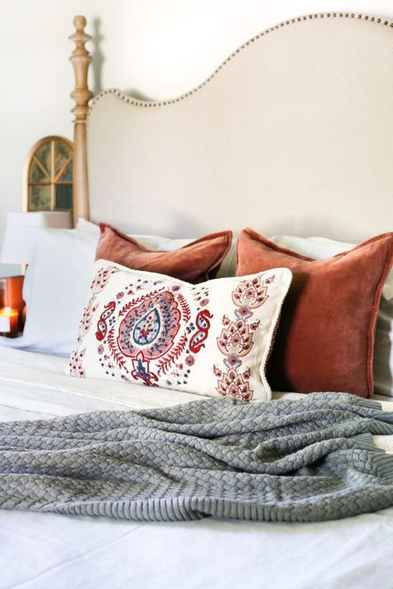 a knit blanket and colorful velvet pillows plus candles for a fall-inspired bedroom
