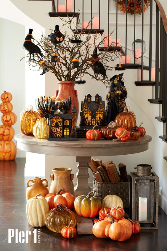 a spooky rustic display with lots of pumpkins in bold shades, cardboard houses and lots of birds