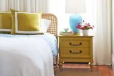 17 a vintage mustard nightstand and matching pillows to add a touch of color