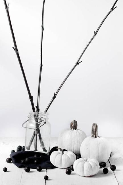 white pumpkins and black beads plus black branches in a clear vase for a stylish minimalist display