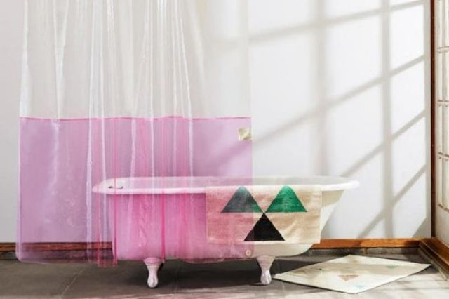 a color block see through shower curtain and a geometric towel to easily make your space trendier