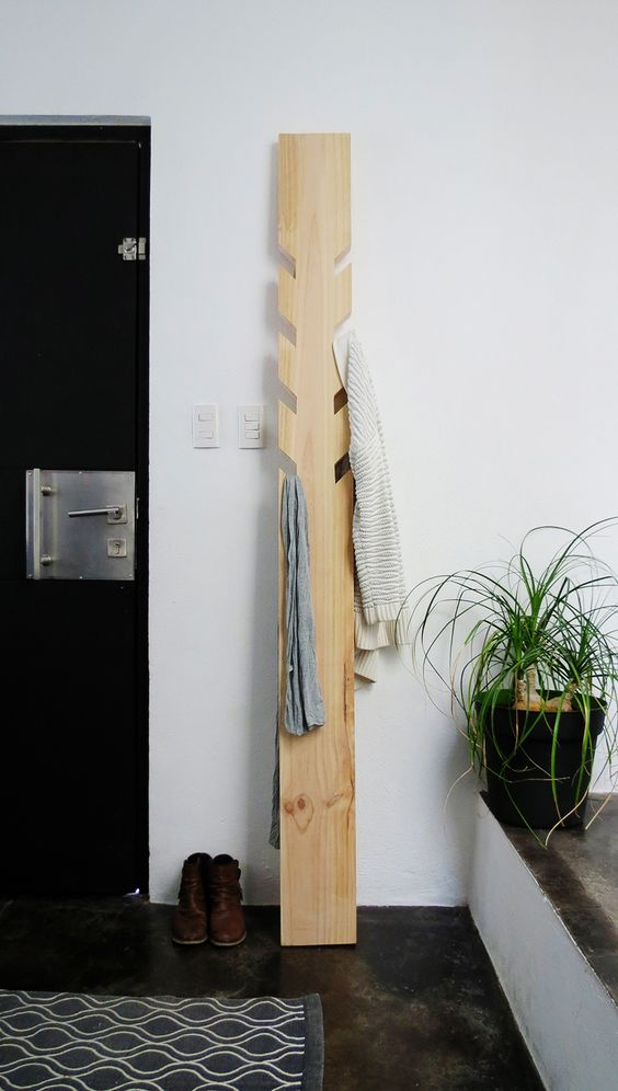 a modern coat rack made of a piece of wood with some hooks cut out is a simple DIY project