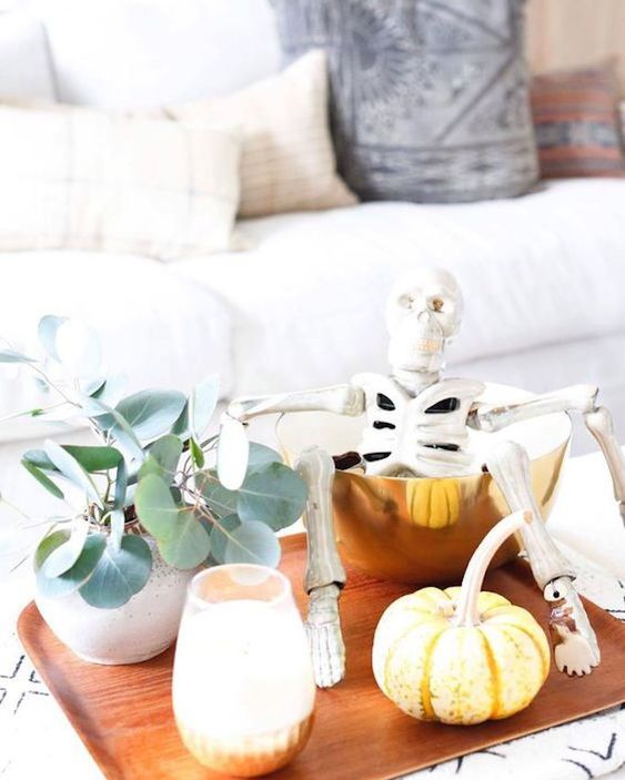 a modern fall display with eucalyptus, pumpkins, candles, a skeleton in a gold bowl on a tray
