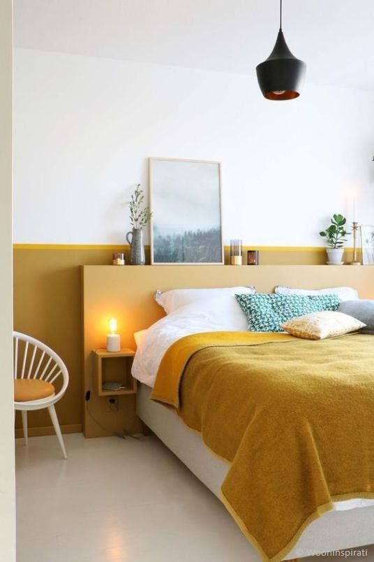 a mustard headboard and wall behind it for a color block effect and a touch of color in the bedroom