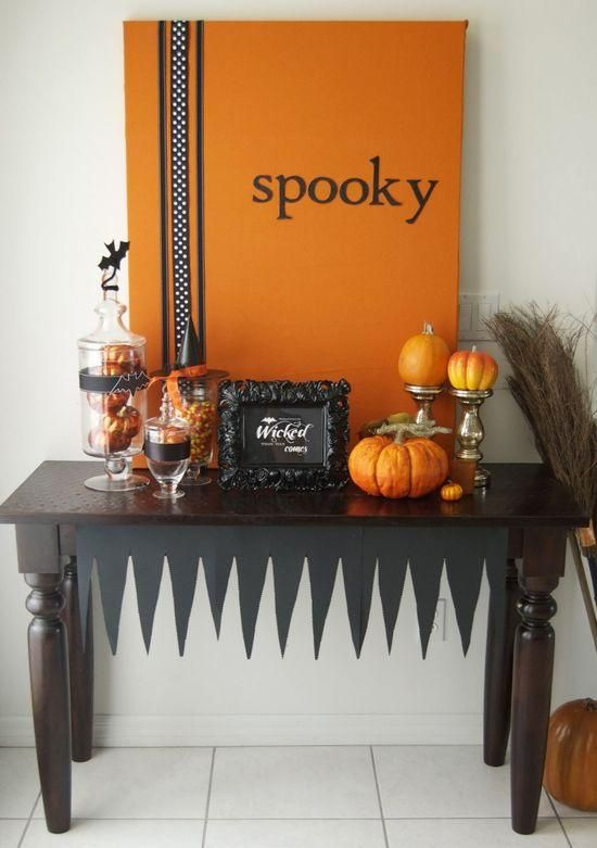 a stylish black and orange console with an artwork, faux pumpkins and glass jars with candies
