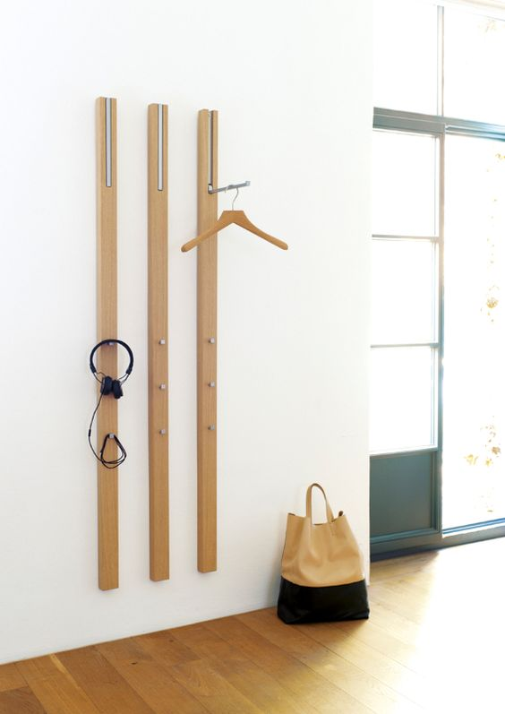 a wall-mounted coat rack of wooden slabs and with metal hooks attached here and there to hang the pieces comfortably
