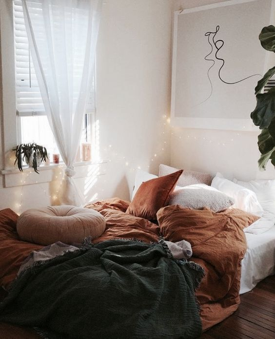 fall-colored bedding in rust color and a dakr grey blanket to subtle embrace the fall