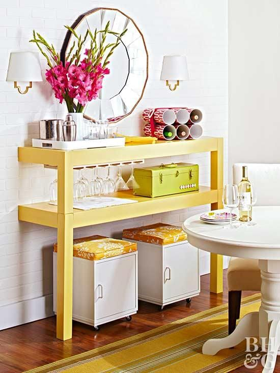 a colorful buffet made of a cut table painted bright yellow, with matchin ottomans