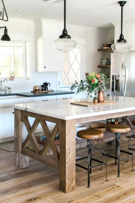 a farmhouse kitchen with a rustic kitchen island of wood and a stone countertop to use as a dining table