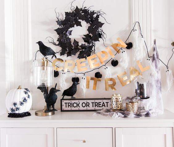 a stylish black, white and gold console with a bunting, a wreath, fake birds and a pumpkin with spiders