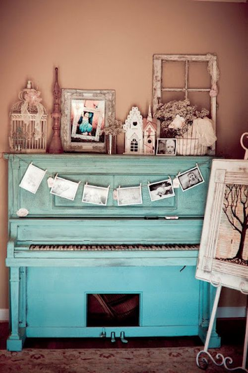a turquoise piano with a photo bunting and a vintage display of various figurines, frames and other items
