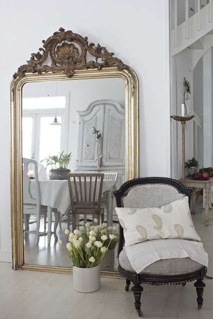 an oversized floor mirror with amazing vintage detailing in gold for a chic and refined entryway