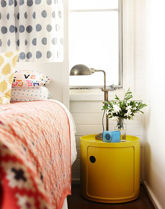 an ultra-modern yellow nightstand of a drum shape makes a statement with color