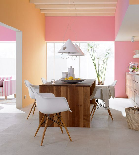 color blocked kitchen walls in pastel pink and orange plus wooden furniture for an inviting eat-in space