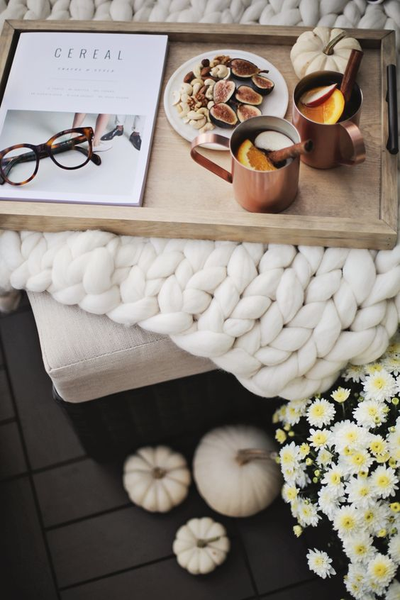 a chunky knit white blanket and copper mugs on a wooden tray are great for fall bedroom decor