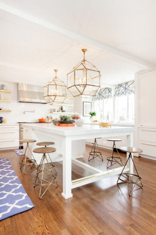 a large white kitchen island that doubles as a dining table and can accommodate many people