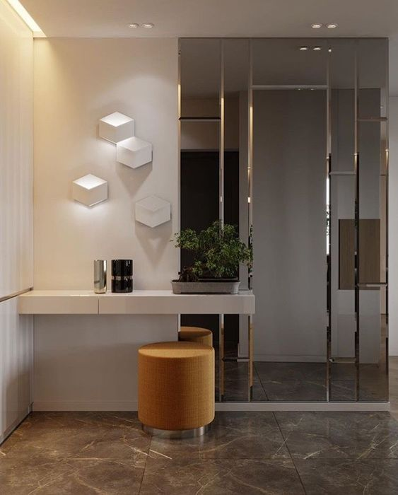 a minimalist entryway with a half mirrored wall, which enlarges the space and makes it bolder