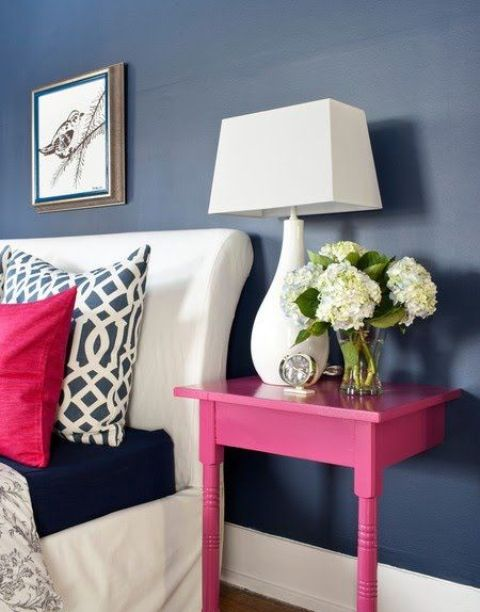 a nightstand made of a cut table and painted hot pink to make a perfect fit for the space