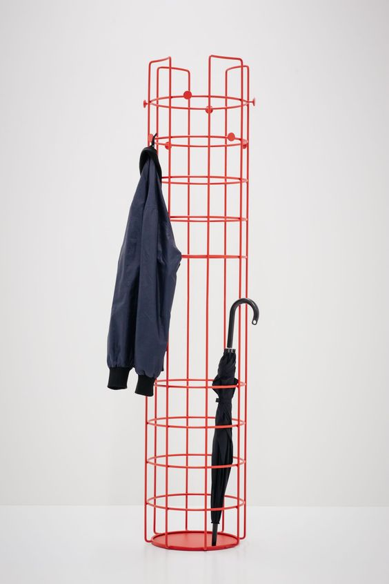 a red metal coat rack features several hooks for hanging and enough storage space for your umbrellas