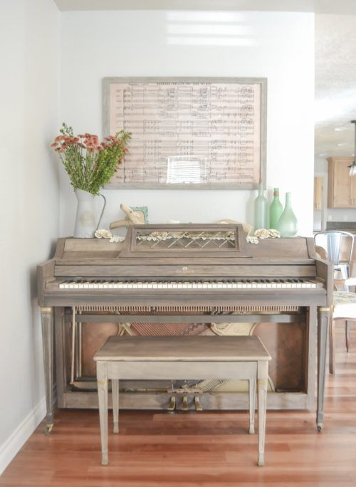 a vintage piano in taupe and a mtching stool, some bottles, a metal jug with blooms and some notepaper as an artwork