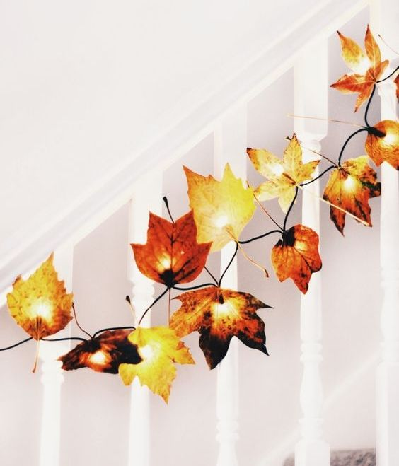 add fake leaves to fairy lights to decorate your home for fall, for example, line up the railing of the stairs