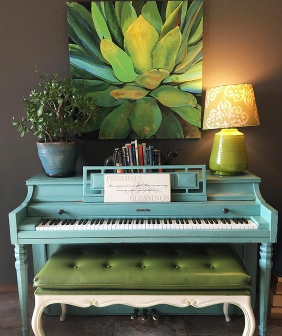 a bright blue piano, a potted plant, a lamp, a stack of books and a bold succulent artwork for a touch of color and interest