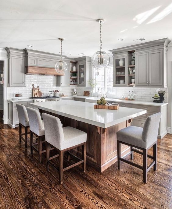 a modern farmhouse kitchen with a large kitchen island of wood and a white ston countertop that doubles as a dining table