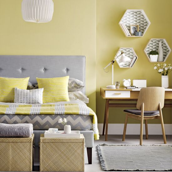 a pale yellow statement wall and matching pillows and a blanket for a colorful touch
