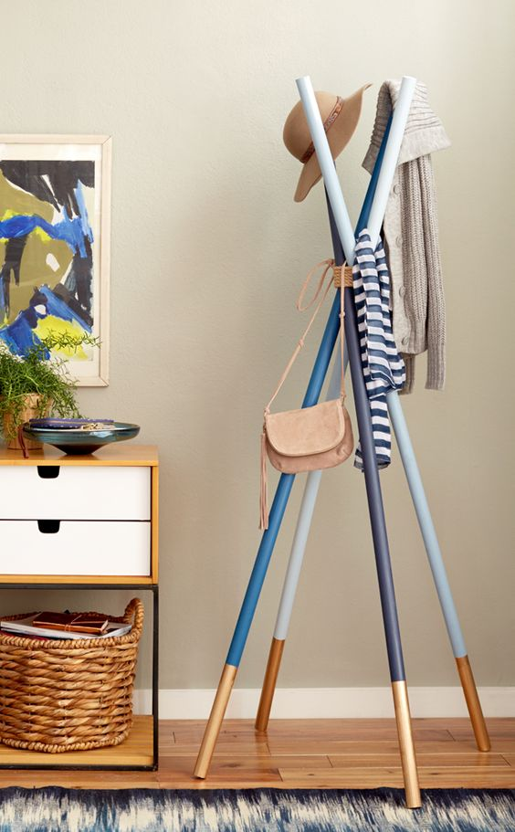 a simple and colorful coat rack of several sticks painted in different colors and metallics for a touch of brightness
