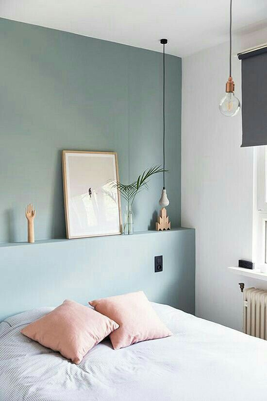 highlight your sleeping zone with a color block effect, paint just one headboard wall in some color, like here - muted green for a peaceful feel