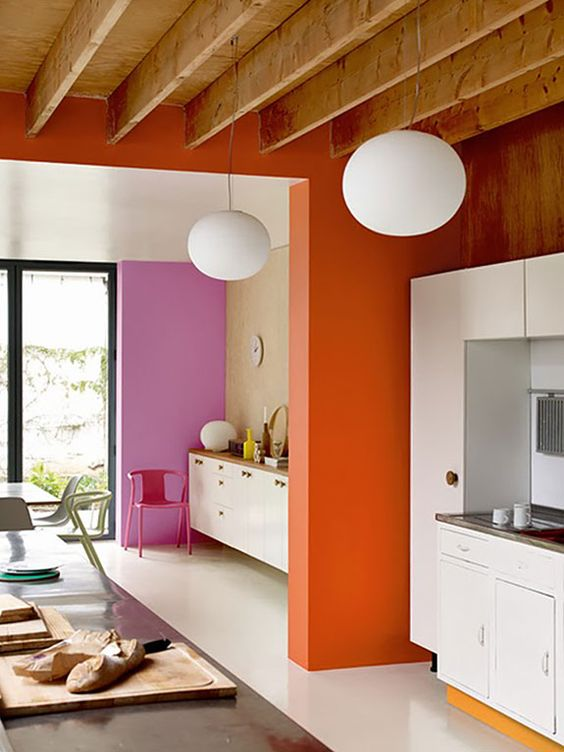 retro-inspired color blocking with a bold pink and orange wall for an accent and all neutrals around