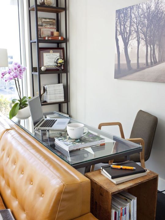 this home office nook uses the blind space behind the sofa, which is usually neglected, and a glass desk makes it airy