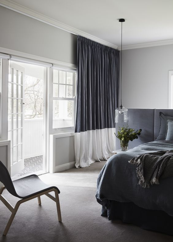 a monochromatic grey and white space with color blocking - a headboard wall and curtains
