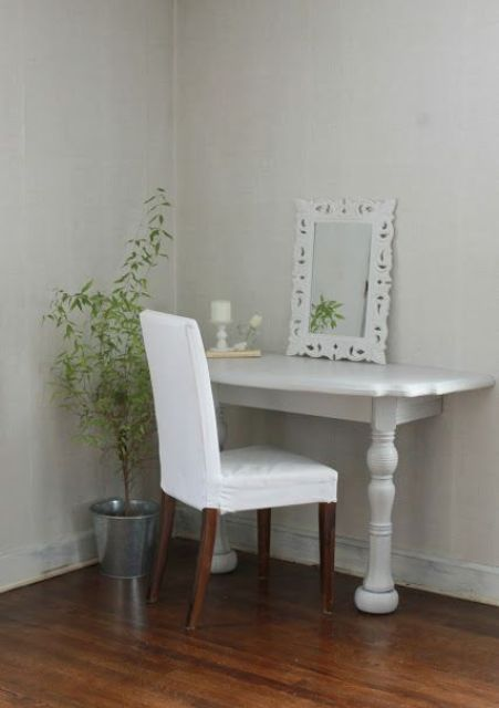 a small makeup nook done in vintage style, with a half cut table and a fabric covered chair