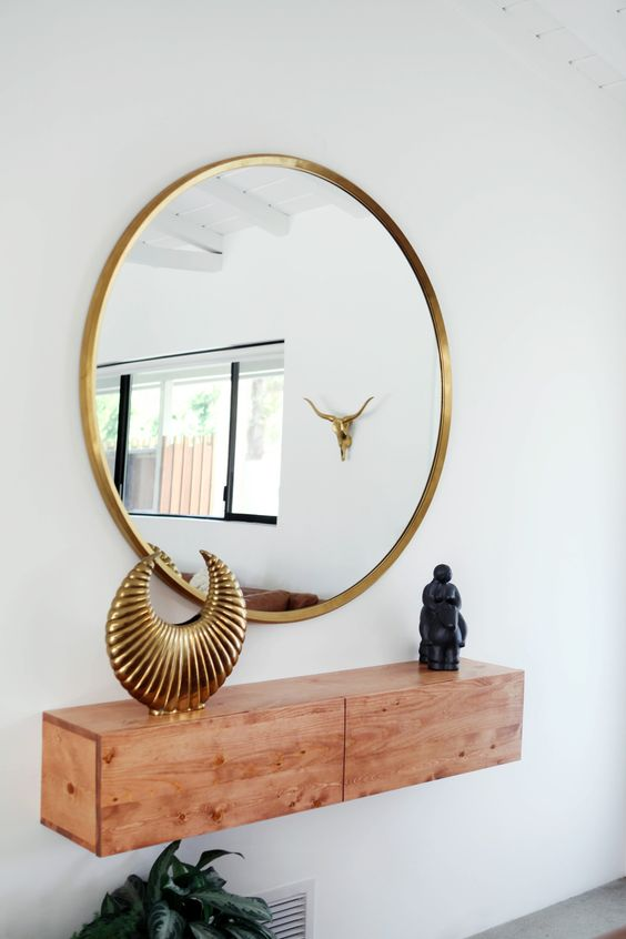 a stylish light colored wood floating console table and a brass framed mirror for a chic entryway
