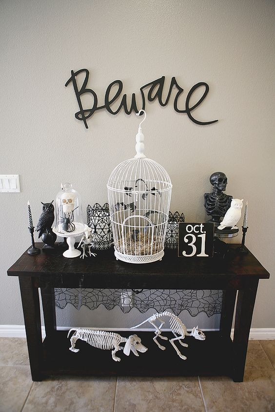 a vintage console table with black and white skeletons of various animals, a cage with bats and black calligraphy over the table