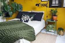 23 a mustard accent wall and touches of dark green and potted plants make up a bold boho space