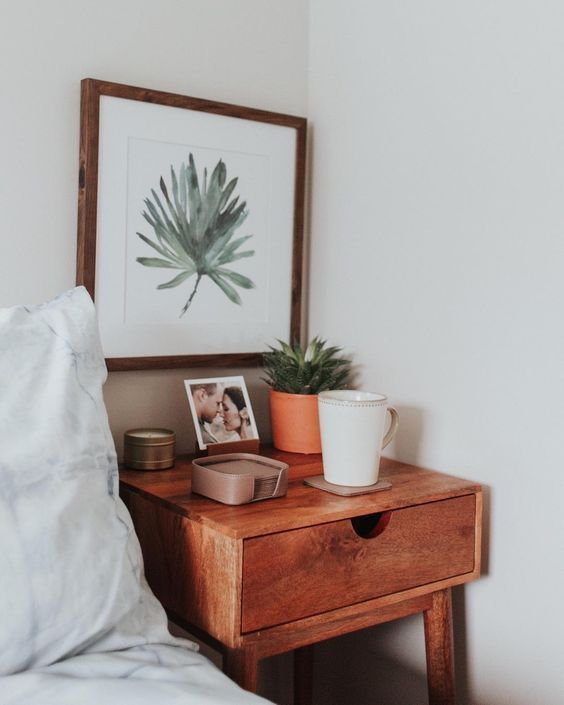 a tightly fitting wooden bedside table with a single drawer