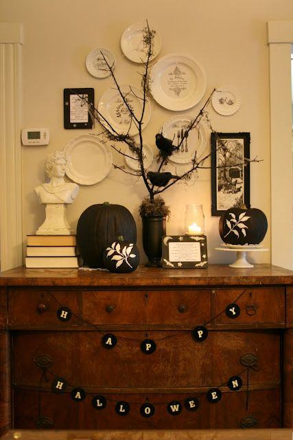 a vintage-inspired display with black and white pumpkins, buntings and blackbirds on branches
