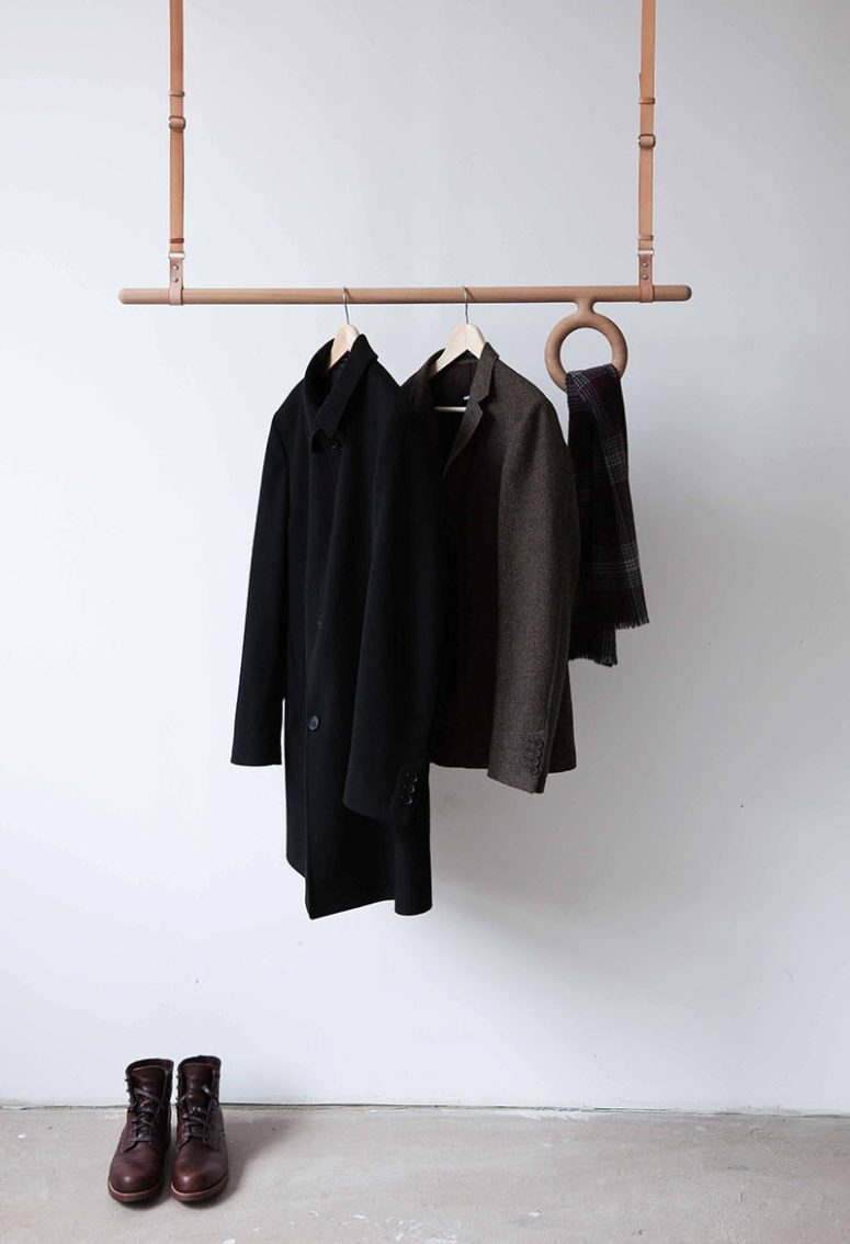 a modern leather and wood coat rack attached to the ceiling is an adjustable piece that offers space for accessories, too