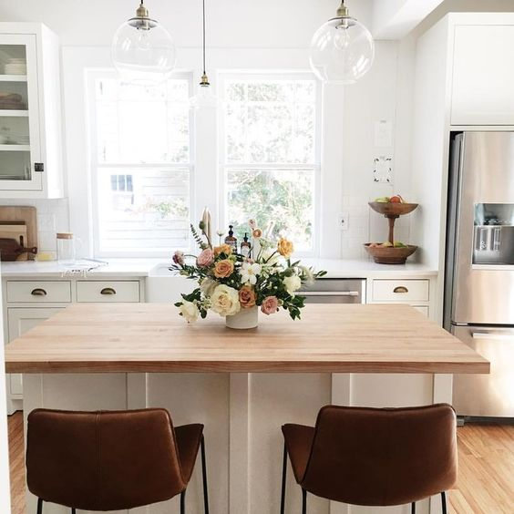 a welcoming space with a wooden tabletop kitchen island and dining table in one, leather stools for sitting