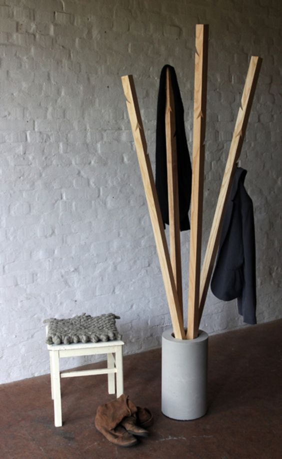 an industrial coat rack with a concrete base and wooden branches with hooks cut in them for a raw touch to your space