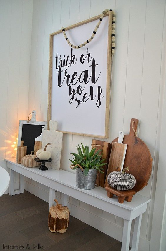an oversized Halloween sign in a frame and some fabric pumpkins and cutting boards on display