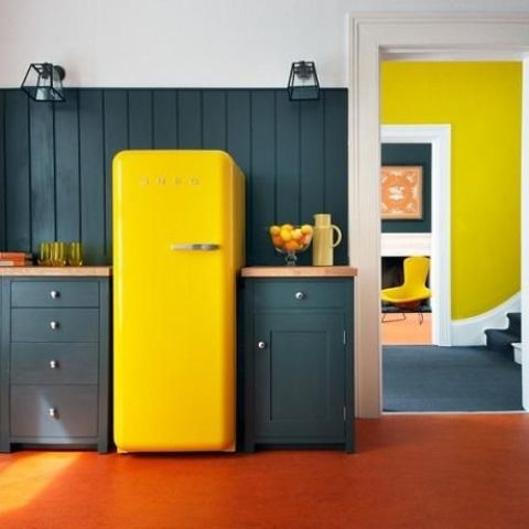 a dark green kitchen is spruced up with a bright yellow fridge for a color block effect