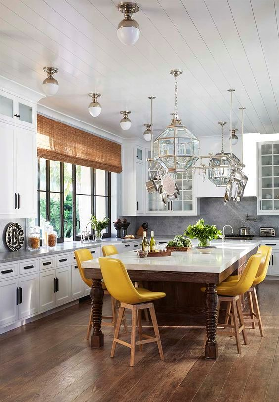 an oversized rustic kitchen island of stained wood and with a white tabletop is used as a dining table