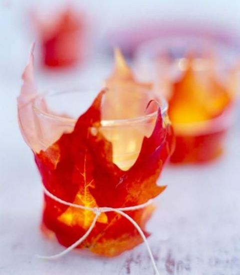 take usual glass candle holders or ready candles and cover them  with fake fall leaves using simple threads