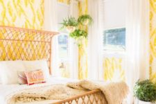 24 bold yellow and white wallpaper with botanical prints create a bright space and a wicker bed adds to it