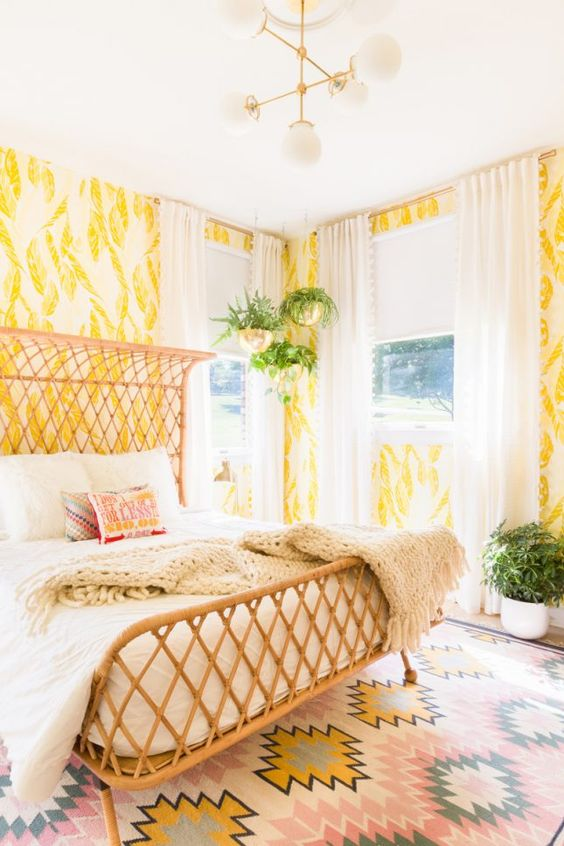 bold yellow and white wallpaper with botanical prints create a bright space and a wicker bed adds to it