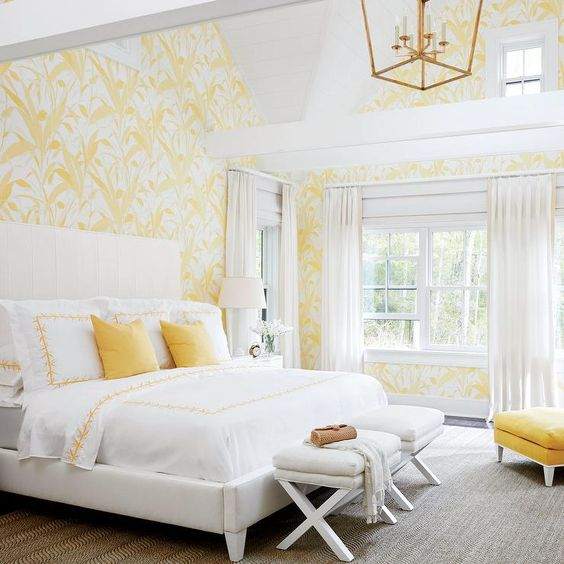 yellow and white wallpaper with botanical prints, yellow pillows and an ottoman for a sun-filled look